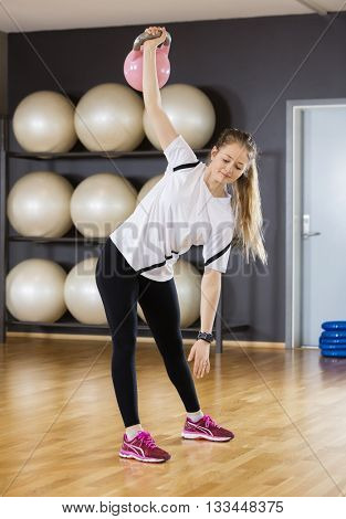Woman Exercising While Lifting Kettlebell At Gym