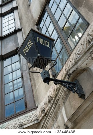 Traditional British police lamp outside London police station.