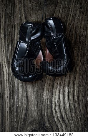 Pair of boxing gloves hanging on wooden wall.