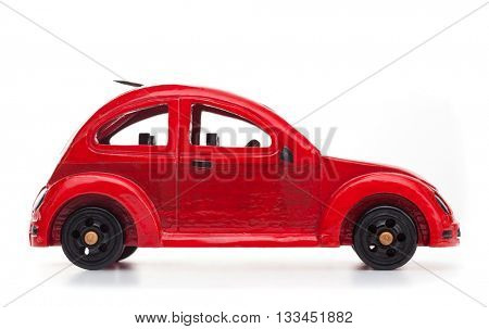 Red retro wooden toy car isolated on white background. Travel concept