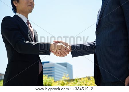 Successful businesspeople shake hands against the sky