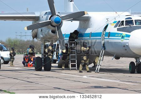 Kiev Region Ukraine - April 24 2012: Special operations sercice squad during the counter-terrosist training with a captured aircrafts with medics helipng the victims on the background