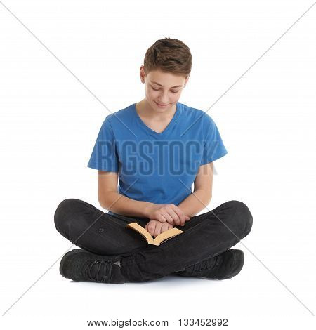 Cute teenager boy with book in blue T-shirt and lotus posture over white isolated background