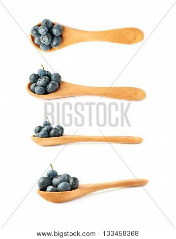 Set of Wooden spoon filled of Ripe bilberry or blueberry over isolated white background