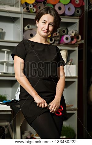 the concept of a confident young woman seamstress designer in the studio. woman holding a pair of scissors and smiling