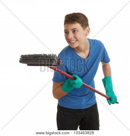 Cute teenager boy in blue T-shirt and green rubber gloves with broom over white isolated background, half body, cleaning concept