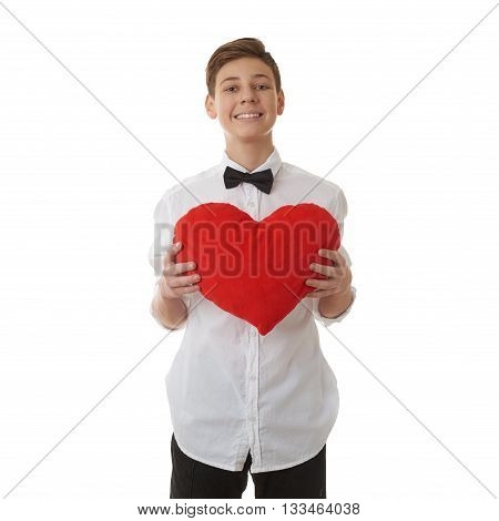 Cute teenager boy in white shirt and black bow tie holding with red plush heart over white isolated background, half body