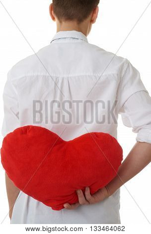 Cute teenager boy in white shirtholding with red plush heart from back over white isolated background, half body