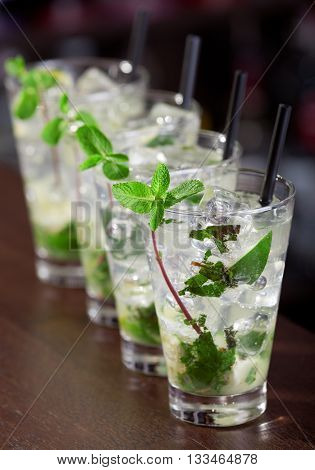 Row of four Mojito cocktails on a bar counter in a club. Vertical shot high angle