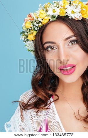 Close-up portrait of an attractive brunette wearing flower diadem isolated on the blue background
