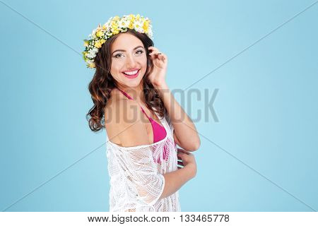 Happy cheerful lady wearing flower diadem isolated on the blue background