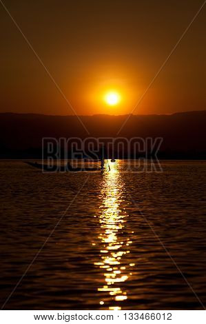 Sunrise at Inle Lake Myanmar. One fishermen on his boat in front of the sun. Vertical shot