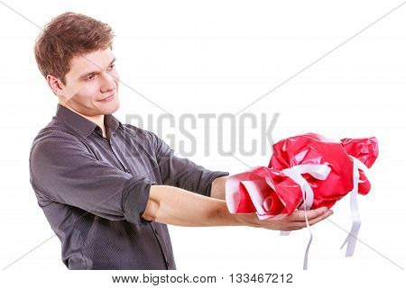 Helping and sharing concept. Young brunet man with big red sweet candy. Celebration and anniversary time. Isolated on white.