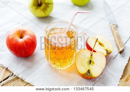 Rustic background with apples and apple juice in glass on homespun napkin.