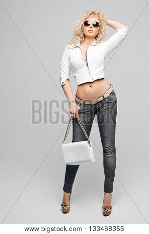 Portrait of beautiful young blonde woman with curly hair. The girl wore a white leather jacket, blue jeans and sunglasses in Studio grey background. Studio portrait. White leather handbag in hand.