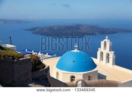 Famous church in Fira Santorini at daytime. Volcano on background