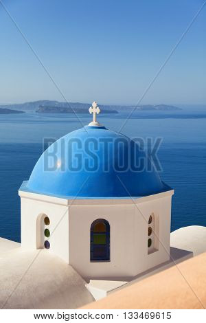 Blue dome church in Oia Santorini Greece. Sea and volcano on background. Vertical shot