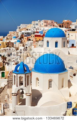 Landscape of Oia town in Santorini Greece with blue dome churches on foreground. Close up vertical shot
