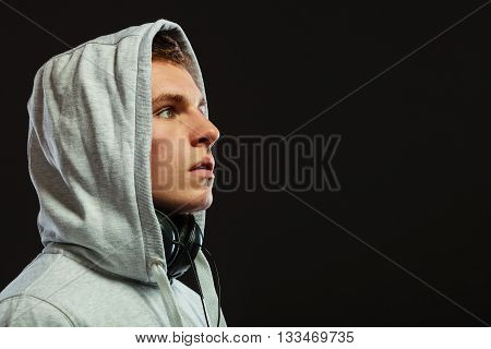 Closeup young handsome hooded man with headphones listening to music sideview dark background