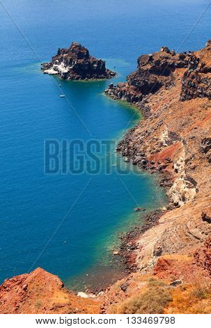 A perfect view of the volcano in Oia Santorini with blue waters of the sea. Vertical shot