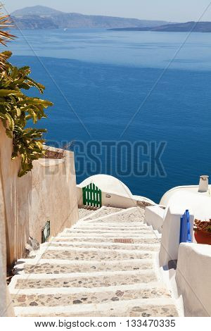 Street view in Oia Santorini. The sea and volcano on background