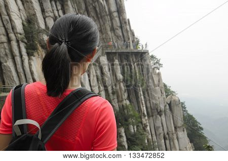 A chinese woman on the cliff walk at Mount Song (songshan) overlooking the sheer cliffs in Henan Province China Dengfeng city.