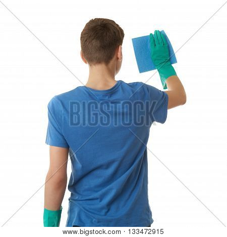 Cute teenager boy in blue T-shirt and green rubber gloves with rag over white isolated background from back, half body, cleaning concept