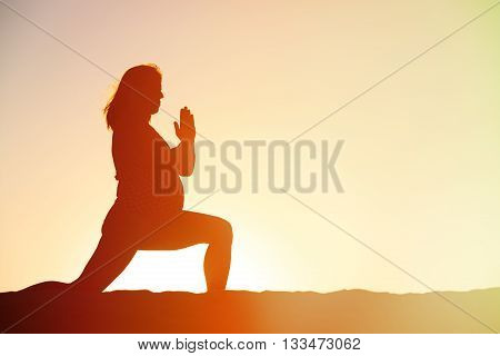 Silhouette of pregnant woman doing yoga on beach, pregnant exercise
