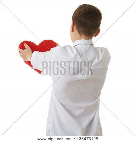 Cute teenager boy in white shirt holding with red plush heart from back over white isolated background, half body