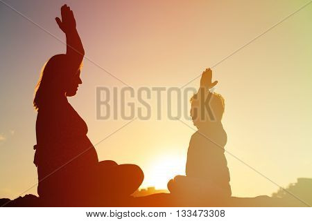 Silhouette of pregnant mother and son doing yoga on beach, family exercise
