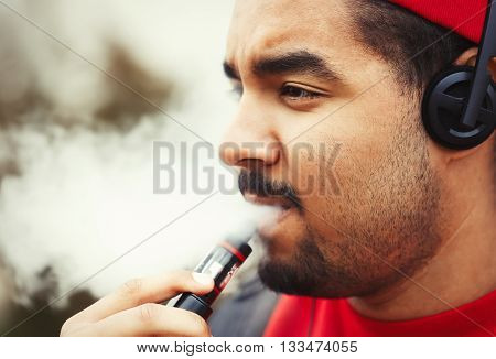 Young Black Man Smoking E-cigarette Vaporizer Device