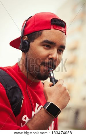Portrait of black boy using modern e-cig vaporizer device for smoking glycerine liquid tobacco with flavor. Popular gadget among young people and who want to improve health and quit smoking