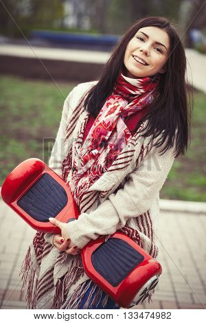 Female model holding modern red electric mini hover board scooter in hands while walking in the park. Popular new gadget. Girl is wearing fashionable boho style clothes.