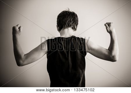 Black And White Rear View Of Teen Flexing Biceps
