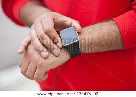 Hands of a African boy using his modern smart wrist watch. This new internet technology lets this person always stay connected to internet and social media.