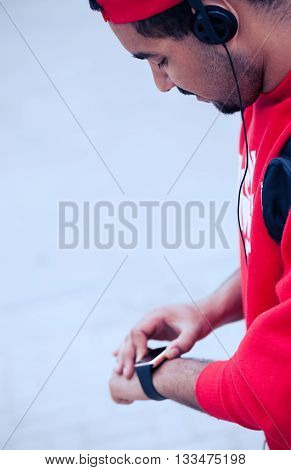 Young African boy using his modern smart wrist watch. This new internet technology lets this person always stay connected to internet and social media.