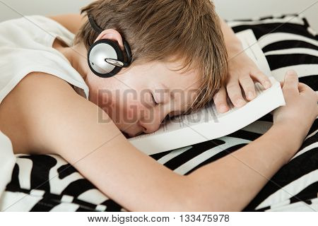 Boy With Headphones Asleep On Top Of Textbook