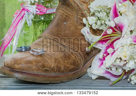 Cowboy boot with engagement and wedding rings and corsage