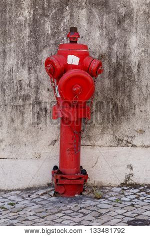 red fire water coming a street hydrant near a wall