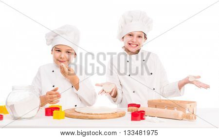 little boy and girl in white uniform kneating dough together