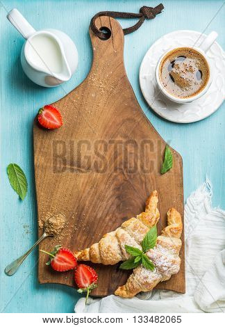 Breakfast or dessert set. Freshly baked croissants with strawberries, cup of coffee and milk in creamer on brown wooden board over blue background, top view, copy space