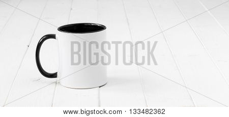 white cup with black handle and inside on planked wooden table