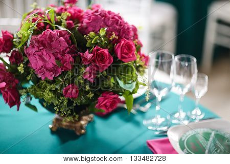 flower arrangement in bowl with pink roses and hydrangea. table setting.