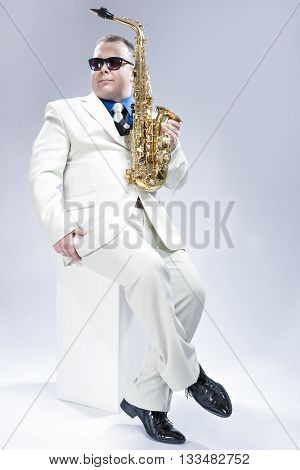 Music Concept. Full Length Portrait of Expressive Caucasian Musician With Alto Saxophone Posing In White Suit Against White Background. Wearing Black Sunglasses.Vertical Image Composition
