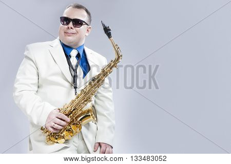 Portrait of Passionate Expressive Male Alto Saxophone Player in White Suit. Posing Against White Background. Horizontal Image Composition