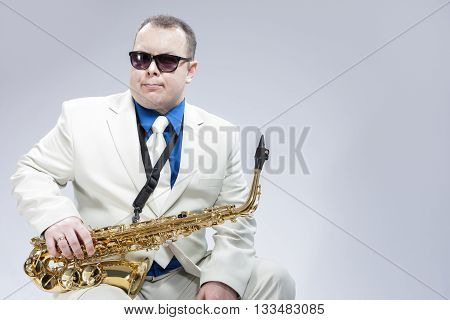 Portrait of Expressive Male Alto Saxophone Player in White Suit. Posing Against White Background. Horizontal Image