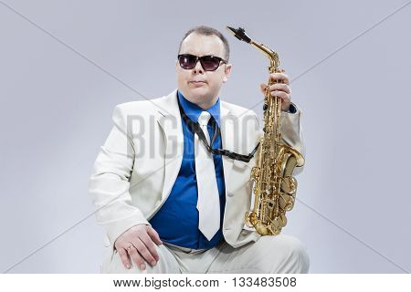 Caucasian Saxophone Player Posing with Instrument In Sunglasses Against White Background. Horizontal Image Composition