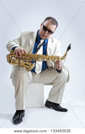 Music Ideas and Concepts. Handsome and Expressive Caucasian Musician With Alto Saxophone Posing In Sunglasses Against White Background. Vertical Shot