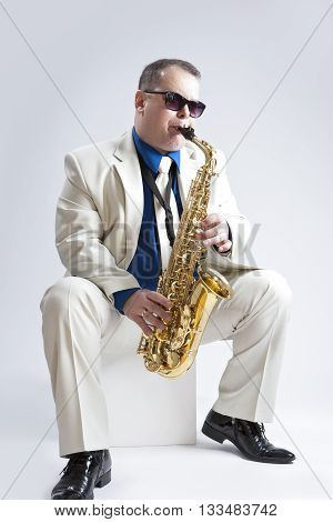 Music Ideas and Concepts. Handsome and Caucasian Music Player Posing In Sunglasse With Saxophone Against White Background. Vertical Image Orientation