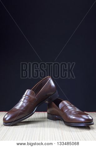 Shoes concepts. Men's Brown Stylish Penny Loafer Shoes On Straw Surface Against Black Background. Vertical Image